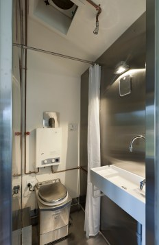 The bathroom is a wet bath arrangement, with showerhead over the sink area, all enclosed in stainless steel. The Incinolet incinerator toilet is tucked in and screened off with a shower curtain when the water is on. A tankless water heater is positioned above the toilet.