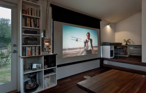 "The large window array next to the door is conveniently sized in 9:16 proportion, and a projector screen hanging above it doubles as a shade. A small LED projector affixed near the bookcase displays a 90"" image, accompanied by speakers on either side of the window. A Dickenson marine propane heater appears to the left of the screen."