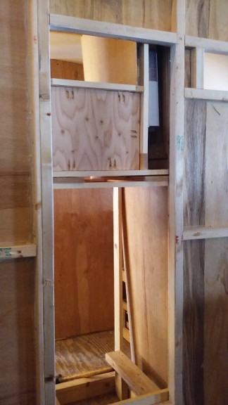 the back of that same cabinet, water heater to the upper right, plumbing space behind the water sorage and water pump storage up top,, behind the food storage