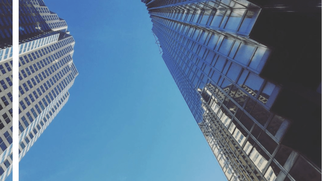 A view from the ground of skyscrapers in Toronto's financial district on a blue-sky day.