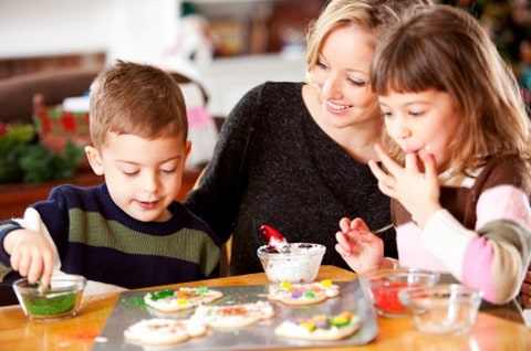 Mother decorating Christmas Cookies with her children