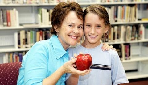 Boy offering an apple to his teacher