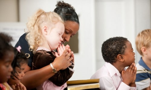 Christian teacher leading in prayer