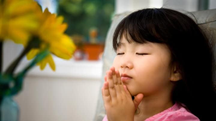 young girl praying with hands raised
