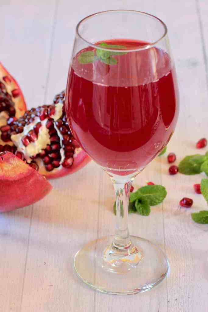 pomegranate juice in a wine glass with mint leaves