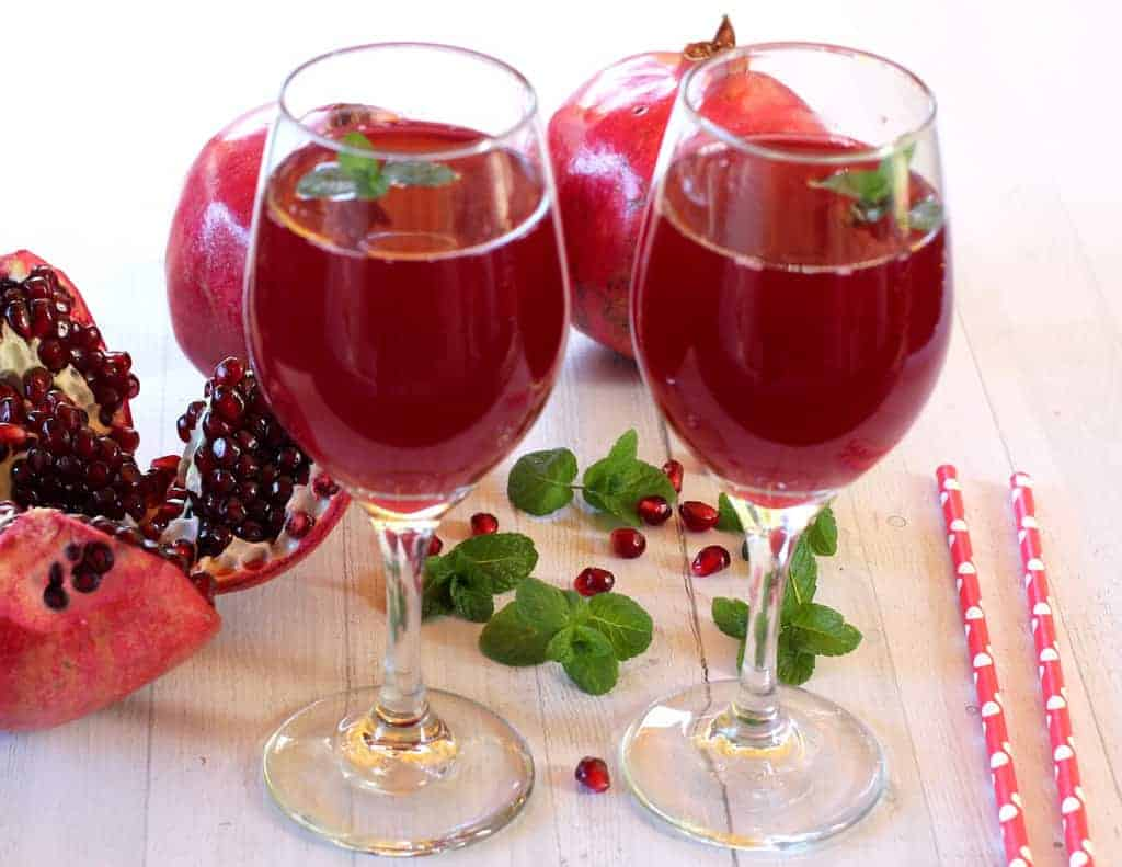 pomegranate juice in 2 wine glasses, with 2 starws on the side and a few pomegranates and mint leaves next to the glasses