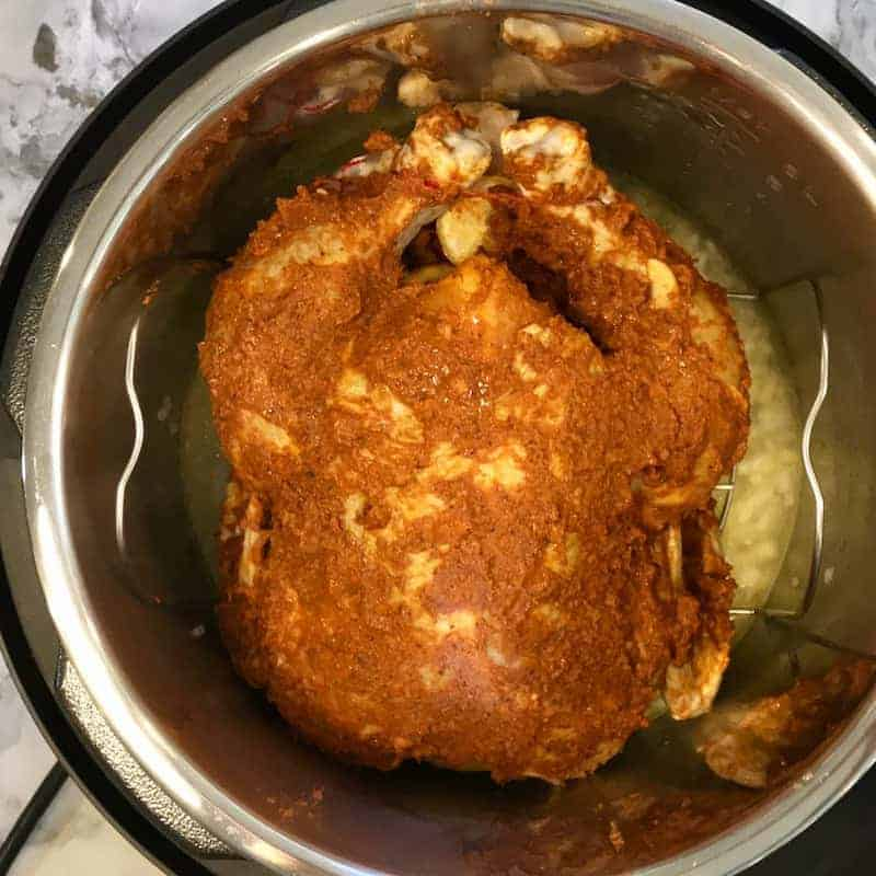Marinated whole chicken is placed on the trivet and the trivet is placed inside the Instant Pot