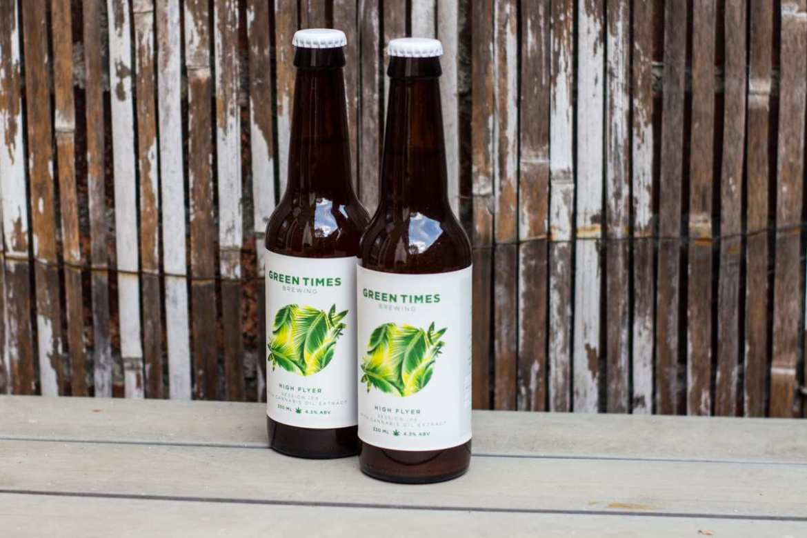 """Two bottles of """"High Flyer"""" CBD Beer sit on a table in front of a worn bamboo backdrop. Brief initial setbacks led the team behind """"High Flyer,"""" a unique CBD beer, to develop a better product including a fully organic formula."""