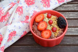 A bowl of oatmeal with fruit, hemp seeds and chia seeds added sits on a wooden picnic table near a folded flower print tablecloth. Hemp oatmeal can supercharge your mornings and help you eat healthier in 2019.