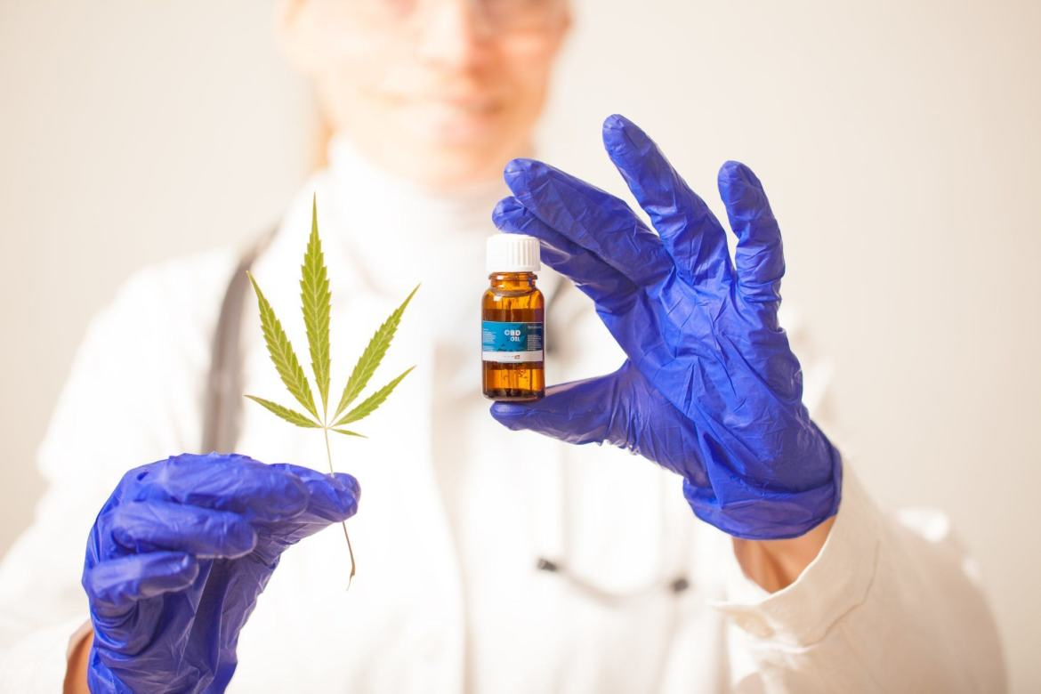A gloved scientist with a vial of CBD and a hemp leaf. Preliminary research supports further investigation into using CBD to treat bipolar affective disorder.