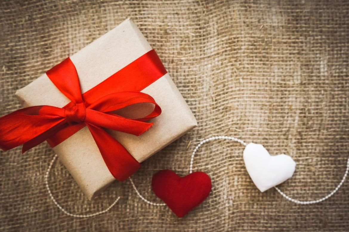 Ministry of Hemp Official Valentine's Day CBD Gift Guide. A gift wrapped with a red ribbon and decorated with hearts on a string, sitting on a fabric background.