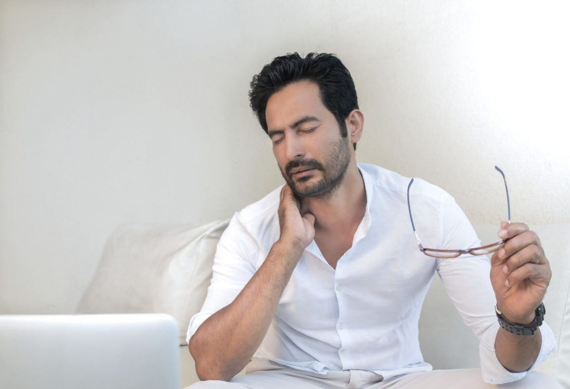 A seated man holds his glasses in one hand while wincing and holding his neck, as if in pain, with the other. Both CBD and THC can relieve symptoms of chronic pain and inflammation in unique ways, both alone and working in concert with other cannabinoids.