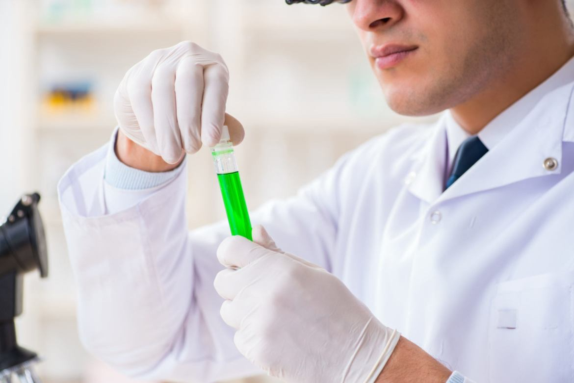 Any brand of CBD oil should be third-party lab tested to ensure purity and reliability. Photo: A scientist in gloves and a white lab coat examines a test tube of green liquid, with a microscope nearby.