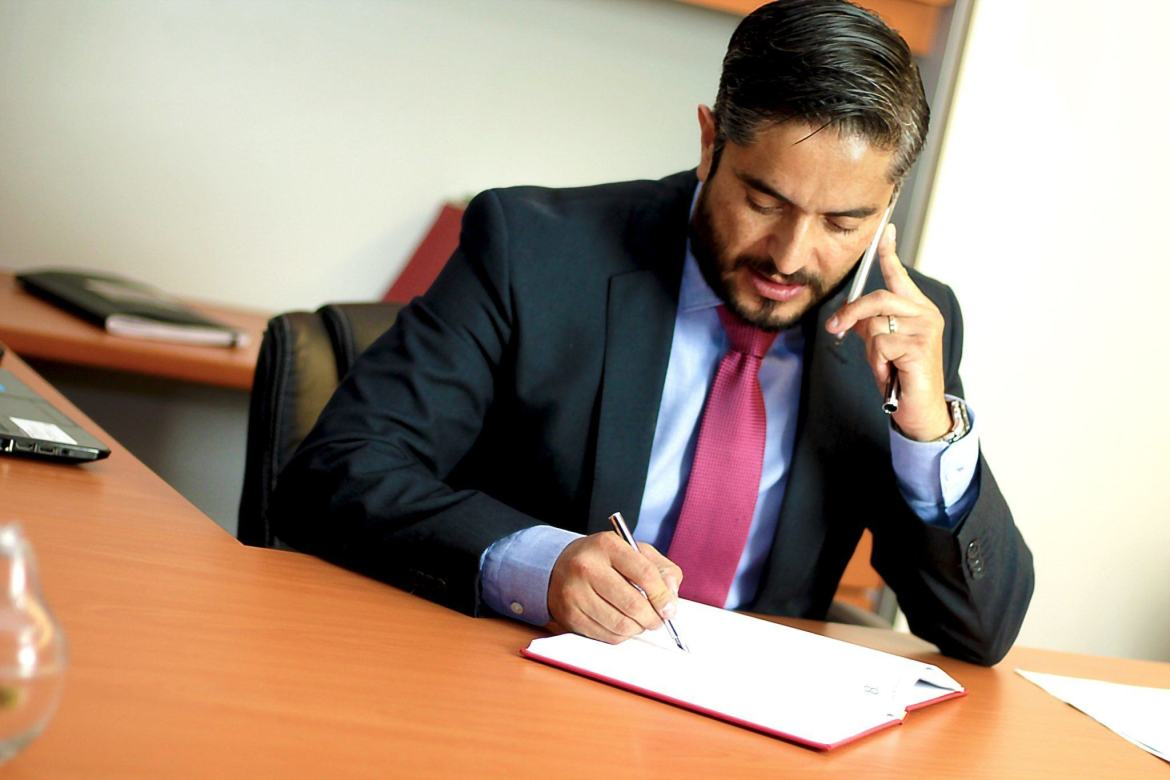 Other factors that increase the cost of CBD include retaining a lawyer, hiring an in-house compliance officer, and the complicated nature of banking and insurance in the hemp and cannabis industries. Photo: A lawyer in a suit and tie writes on a notepad while talking on a smartphone in an office.