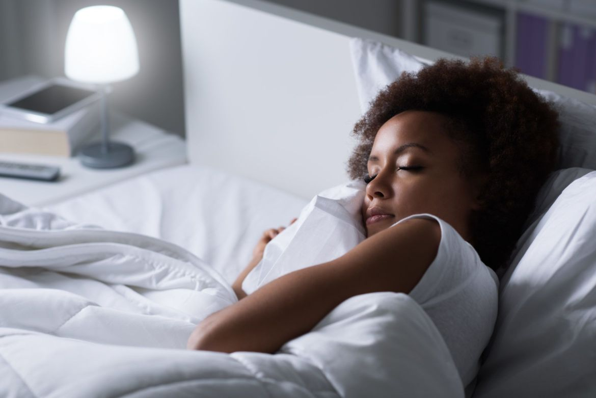 Using CBD for sleep may increase melatonin levels and help ease health conditions that cause insomnia. Photo: A dark-skinned woman sleeps on a bed with white sheets, while a light shines on a nightstand.