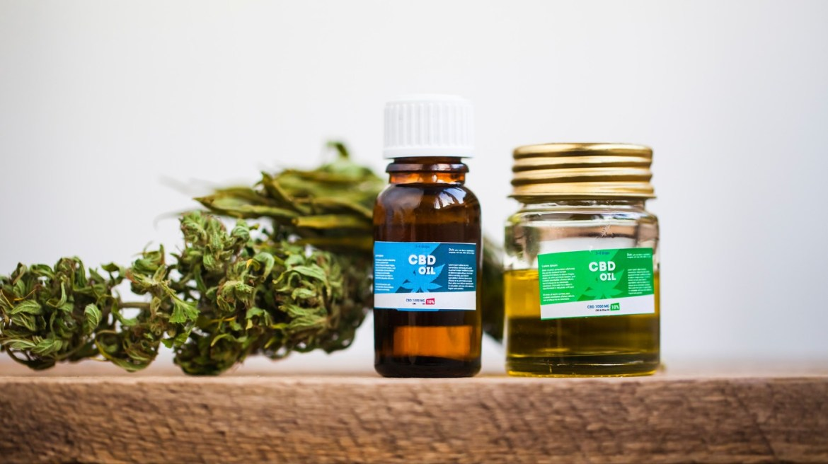 CBD offers numerous benefits without a high, unlike kava which can cause mild mind-altering effects. Photo: CBD oil bottles posed on a wooden table with hemp buds.
