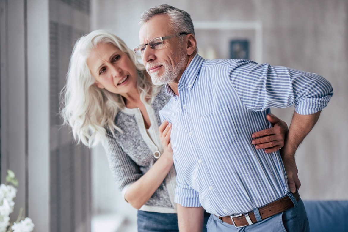 While CBD may offer pain relief, knowing how to pick the best CBD oil for pain can be confusing. Photo: An older woman helps an older man who is clutching his back in pain.