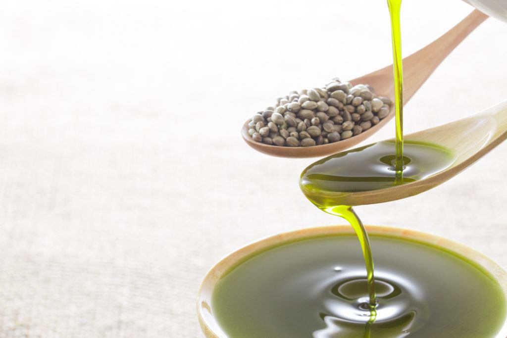 Hemp seeds and hemp seed oil in a spoon, with the oil overflowing into a bowl. We discuss how hemp seed oil is made and making hemp seed oil at home.