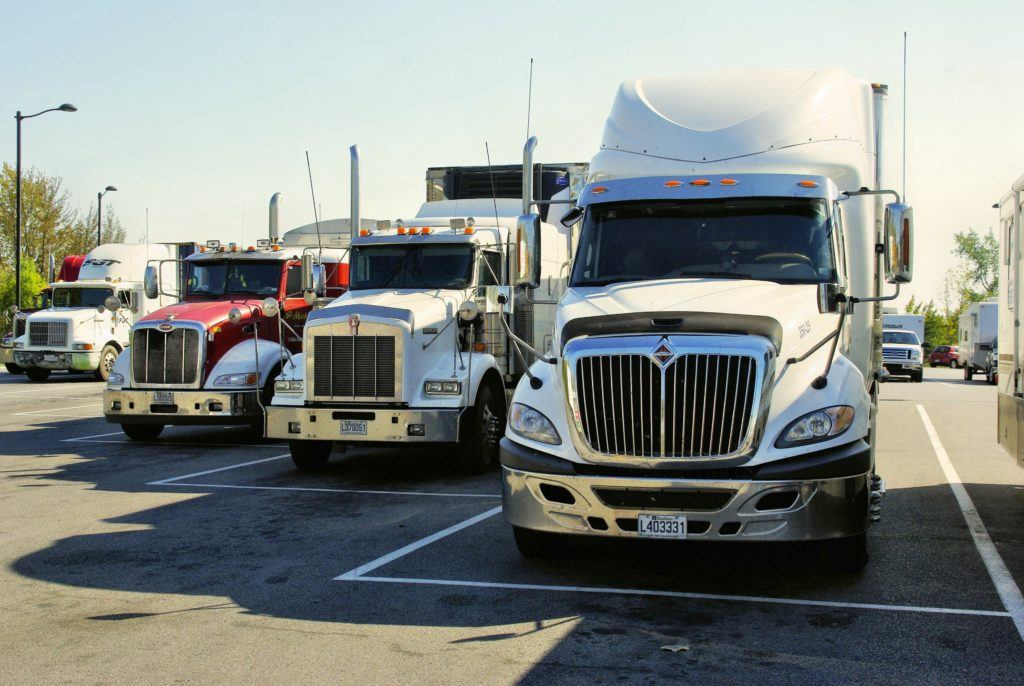 Recent arrests of truckers with hemp in Idaho and elsewhere are a troubling sign of the confusing legal landscape around hemp. Photo: A row of tractor trailor trucks lined up in a parking lot.