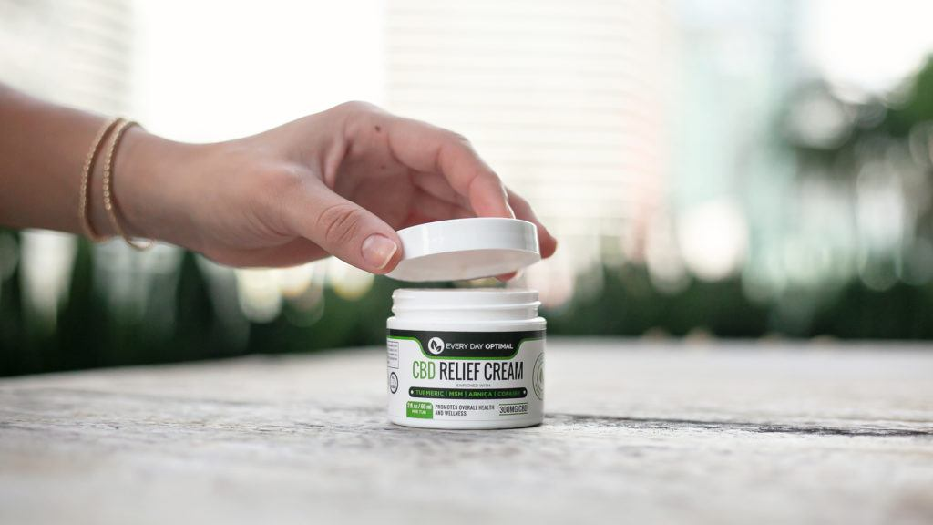 It's important to choose top-quality CBD products made from lab-tested, U.S. grown hemp. Photo: A hand opens a jar of Every Day Optimal CBD cream