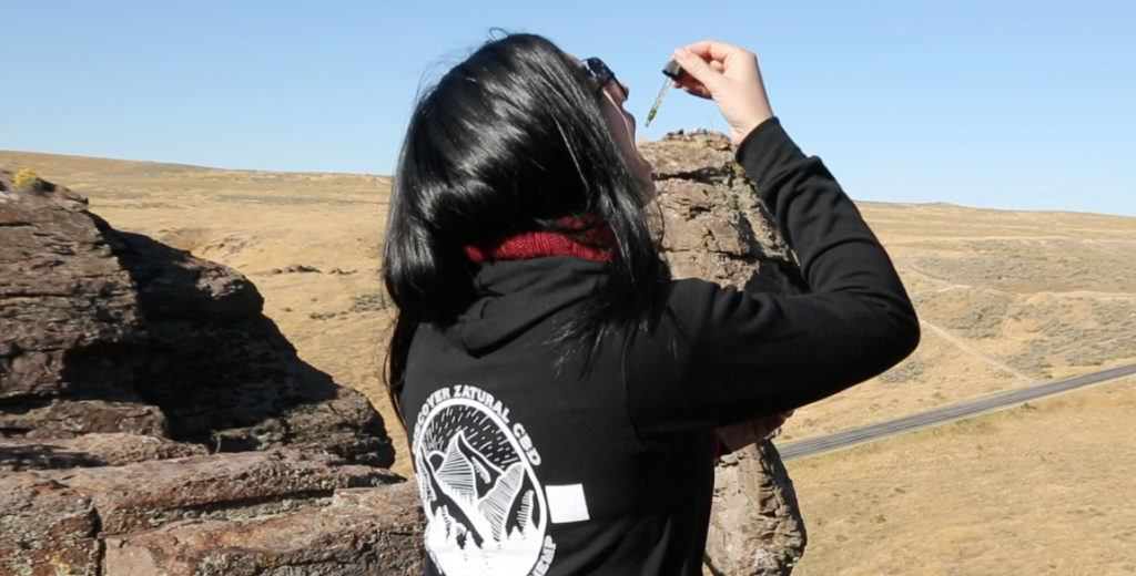 We were surprised by how effectively Zatural CBD Oil Drops helped us feel better. Photo: In a desert setting, a woman in a Zatural-branded hoodie takes CBD oil from a dropper.