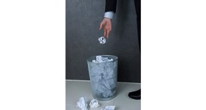 Businessman putting crumpled paper into wastepaper basket