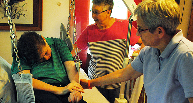 """Sharon Kowalski comes home for spa day to her legal guardian, Karen Thompson, center, and Thompson's wife, Patty Bresser, right. Here she is transported in a Hoyer lift. Kowalski's parents denied her contact with Thompson after she was injured, but after lengthy litigation Thompson prevailed and began caring for Kowalski. Then Court of Appeals Judge Jack Davies wrote, in 1991 that """"Thompson and Sharon are a family of affinity, which ought to be accorded respect. (Photo courtesy of Benjamin R. Kwan)"""