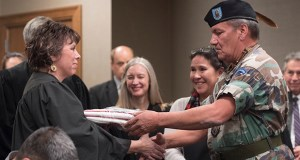 Robert Durant, right, a veteran with the White Earth Honor Guard, presents the White Earth Nation tribal flag to Supreme Court Justice Anne McKeig. (Photo: Craig Lassig)