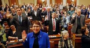 State Rep. Jeanne Poppe, left, D-Austin, joins Minnesota House colleagues with hands raised to take the oath of office as the 2019 Legislature convened Tuesday in St. Paul. (AP Photo: Jim Mone)
