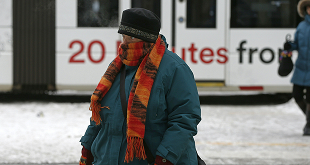 A woman dressed for the cold braves frigid sub-zero temperatures as she crosses a street Jan. 31 in downtown Minneapolis as the arctic blast continued. (AP photo: Jim Mone)