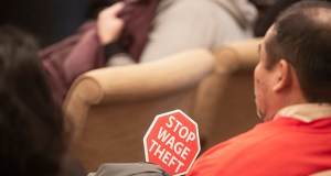 A worker on Feb. 6 holds an anti-wage-theft sign during a hearing on House File 6, a bill from Rep. Tim Mahoney, DFL-St. Paul, that creates a gross misdemeanor for employers who withheld wages from employees. (Staff photo: Kevin Featherly)