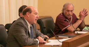 Lobbyist Joel Carlson testifies in conference committee against a cooperative divorce bill, while proponent Andy Dawkins looks on. Dawkins, a former DFL House member, came to the hearing straight from a softball game, still in uniform. (Staff photo: Kevin Featherly)