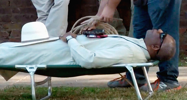 In this April 17, 2018, file image from video provided by KTHV-TV, a death penalty protester outside the Arkansas governor's mansion in Little Rock prepares to tie rope around Pulaski County Circuit Judge Wendell Griffen who is lying on a cot in protest of executions. (AP file photo: KTHV/TEGNA Inc.)