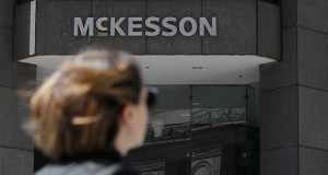 A pedestrian walks across the street from a McKesson sign on an office building in San Francisco last month. McKesson is one of the opioid companies in settlement talks with state attorneys general. (AP photo)