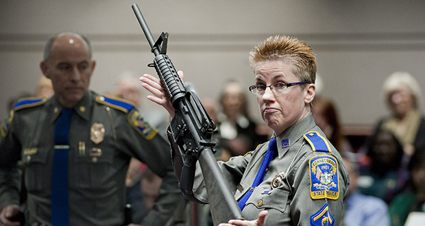 In this 2013 file photo, Barbara J. Mattson of the Connecticut State Police holds up a Bushmaster AR-15 rifle, the same make and model of gun used in the Sandy Hook School massacre, during a legislative hearing in Hartford, Connecticut. (AP file photo)
