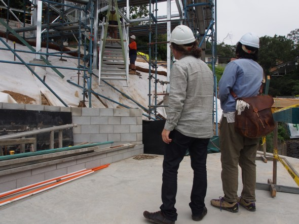 Architects nervously watching the final piece of stair being coaxed into place.