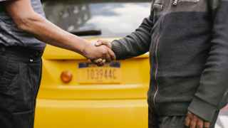 ethnic men shaking hands near taxi