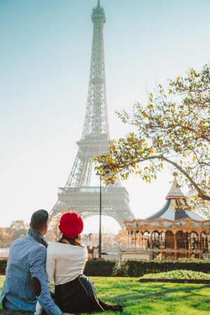 Travel couple in front of merry-go-round in Paris