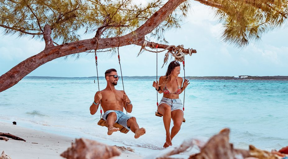 Traveling couple on the beach in Bahamas on swings