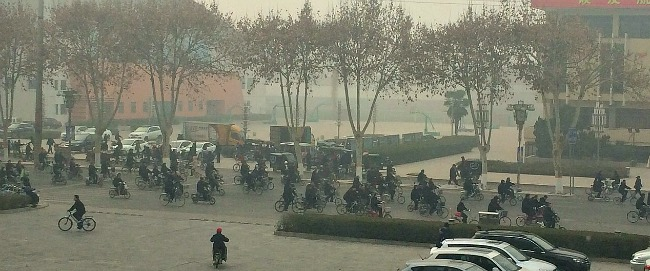 China: Factory workers leaving on their bikes for lunch. Road closed while they ride home for a 2 hour break.