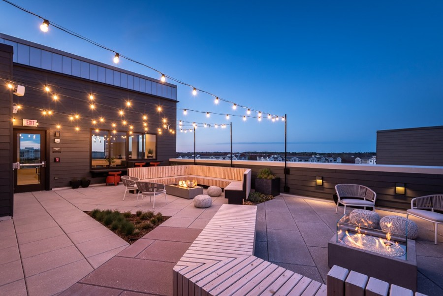 rooftop lounge with firepits tv and a great view overlooking southfield