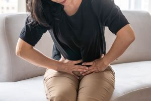 Woman sitting on couch with pelvic pain