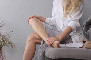 woman sitting on couch with Varicose Veins