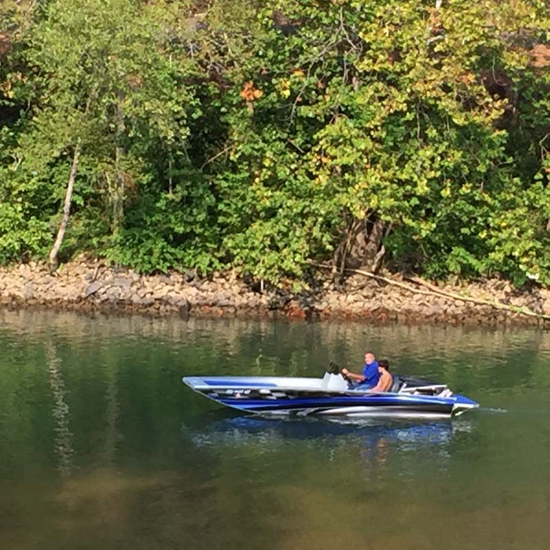 two people driving a blue boat