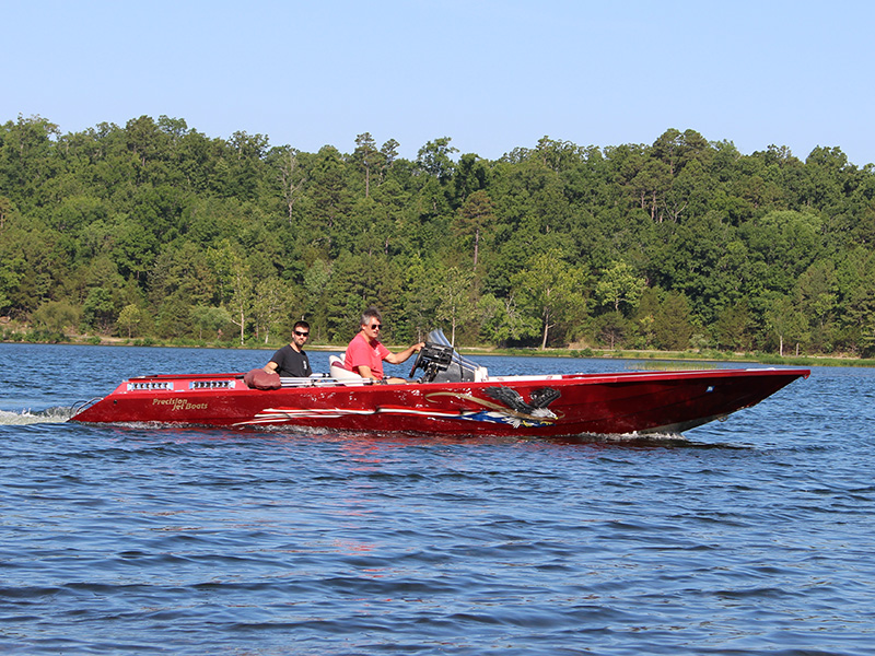 red speedboat idling on a lake