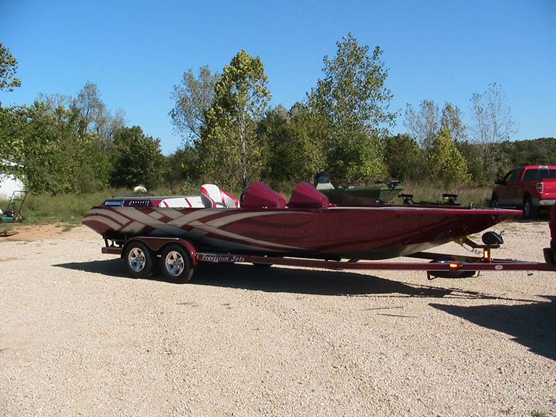 burgundy and gray boat on a trailer