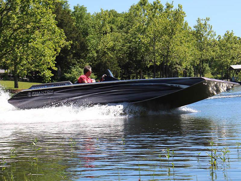 man driving a black speedboat