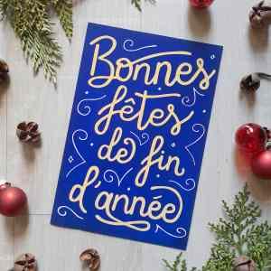 Carte de voeux à commander, avec message de Bonnes fêtes de fin d'année, écrit en jaune sur fond bleu nuit.