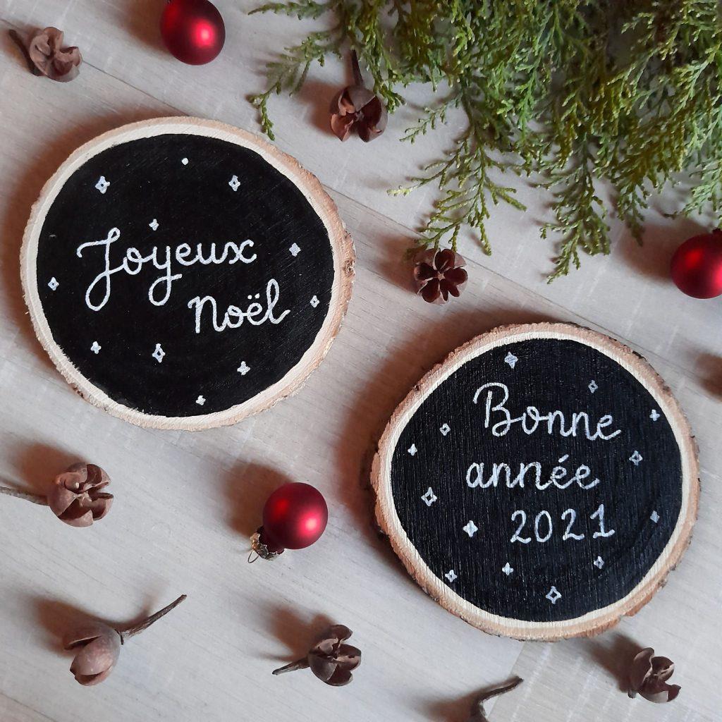 Deux rondins de bois peints en noir avec message de joyeux noël et bonne année 2021 calligraphiés en blanc