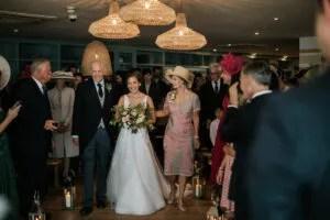 bride walking down isle of her Chic September Hotel Wedding